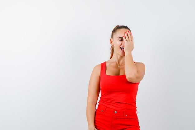 Młoda dama w czerwonym podkoszulku, czerwonych spodniach, trzymając rękę na twarzy i patrząc wesoło, widok z przodu.