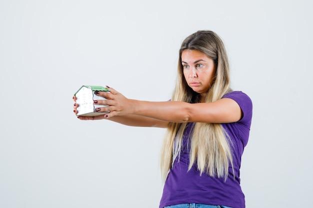 Młoda dama w fioletowej koszulce patrząc na model domu i patrząc wątpliwie z przodu.