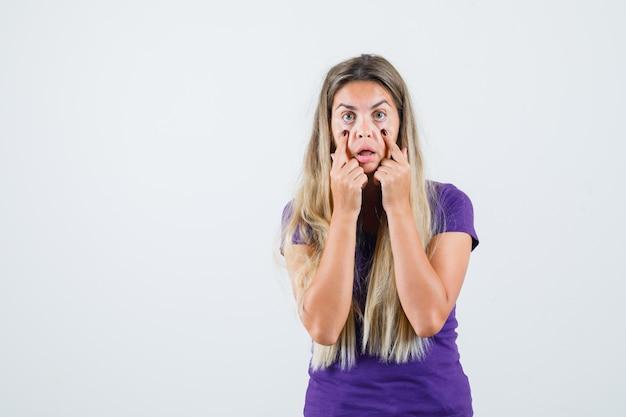 Młoda dama w fioletowej koszulce ściąga powieki palcami, widok z przodu.