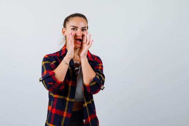 Młoda dama w górnej, kraciastej koszuli z rękami przy ustach, aby powiedzieć sekret i wyglądać na podekscytowaną, widok z przodu.