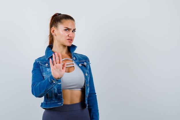 Młoda dama w górze, dżinsowa kurtka pokazująca gest zatrzymania i wyglądająca na pewną siebie, widok z przodu.