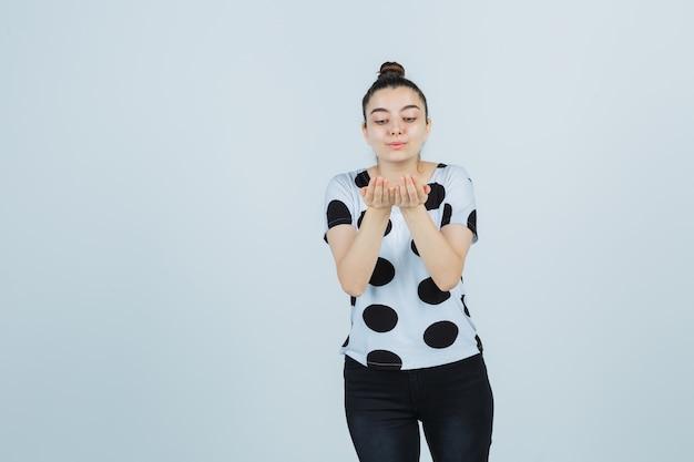 Młoda dama w koszulce, dżinsach wysyłających buziaka w dłonie i wyglądająca uroczo, widok z przodu.
