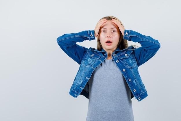 Młoda dama w koszulce, dżinsowej kurtce, spódnicy trzymającej ręce na głowie i wyglądająca na zapominalską