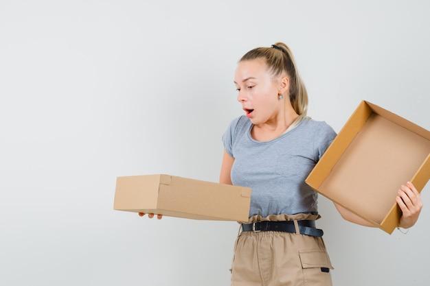 Młoda dama w koszulce i spodniach, patrząc w karton i wyglądająca na zdumioną