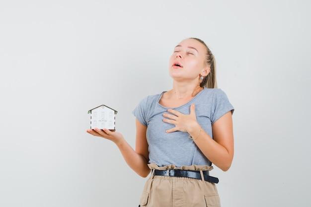 Młoda dama w koszulce i spodniach trzyma model domu i wygląda na wdzięczną