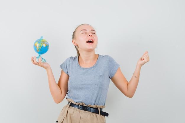 Młoda dama w koszulce i spodniach trzyma szkolną kulę ziemską i wygląda błogo