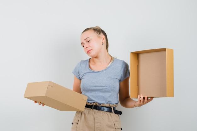 Młoda dama w koszulce i spodniach zaglądająca do kartonu i wyglądająca na rozczarowaną