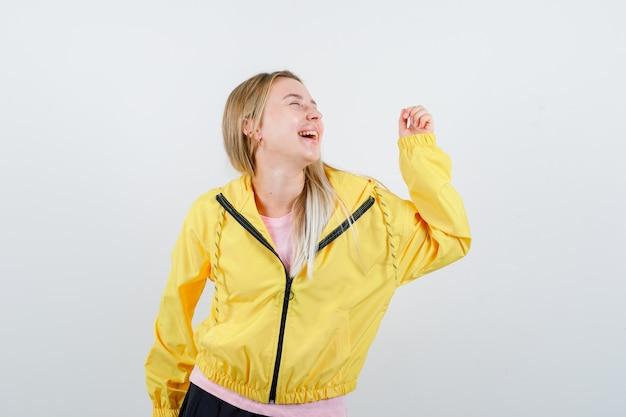 Młoda dama w koszulce, kurtce pozuje stojąc i patrząc energicznie