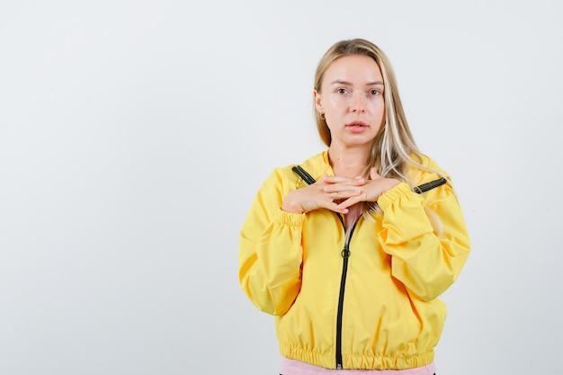 Młoda dama w koszulce, kurtce, trzymając się za ręce na piersi i wyglądająca na pewną siebie