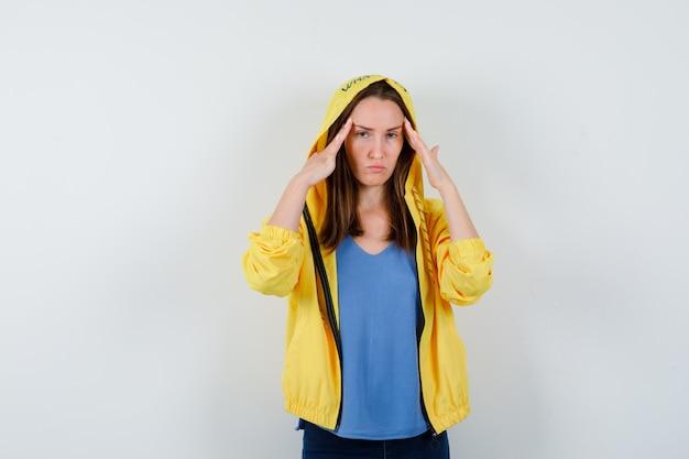 Młoda dama w koszulce, kurtce trzymającej palce na skroniach i wyglądającej na zmęczoną, widok z przodu.