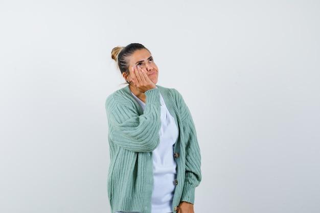 Młoda dama w koszulce, kurtce trzymającej rękę na policzku i wyglądającej na zamyśloną