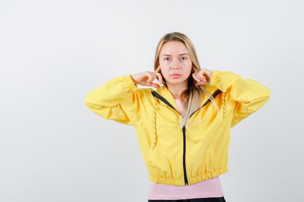 Młoda dama w koszulce, marynarce zatykająca uszy palcami i wyglądająca na zirytowaną