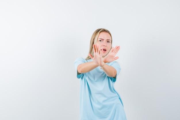 Młoda dama w koszulce pokazująca gest odmowy i wyglądająca na przestraszoną, widok z przodu.