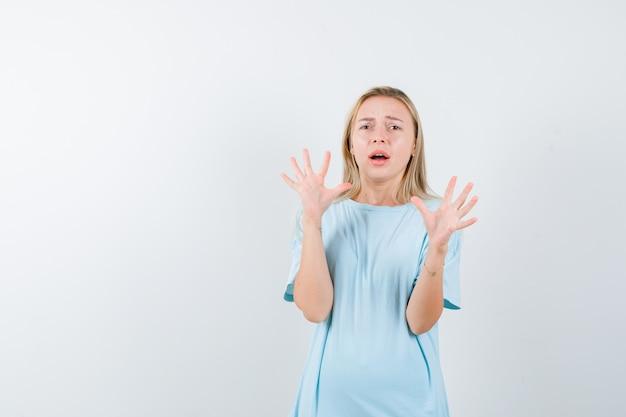 Młoda dama w koszulce pokazuje dłonie w geście kapitulacji i wygląda na przestraszoną, widok z przodu.