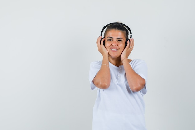 Młoda dama w koszulce, słuchanie muzyki w słuchawkach