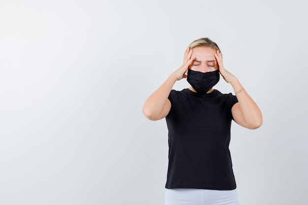 Młoda dama w koszulce, spodniach, masce medycznej trzymającej ręce na głowie na białym tle