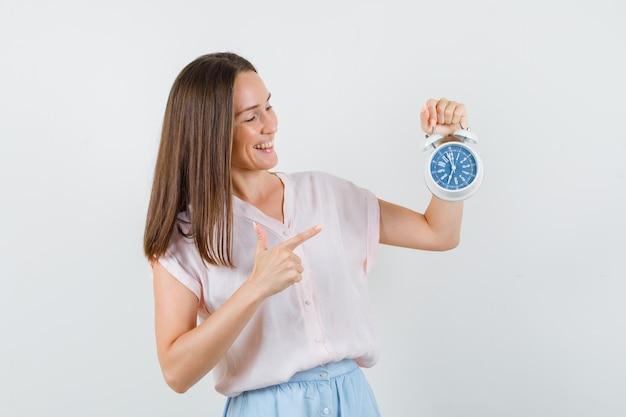 Młoda Dama W Koszulce, Spódnicy, Wskazując Na Budzik I Patrząc Radośnie, Widok Z Przodu. Darmowe Zdjęcia