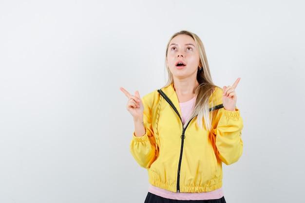 Młoda dama w koszulce, z kurtką wskazującą na bok i wyglądająca na zdziwioną