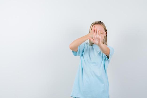 Młoda dama w koszulce zakrywającej oczy ręką, pokazując gest zatrzymania na białym tle