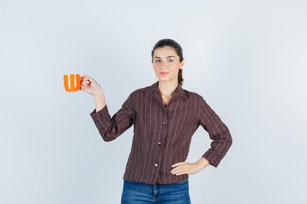 Młoda dama w koszuli, dżinsy pokazujące filiżankę, z ręką w talii i wyglądającą ładnie, widok z przodu.