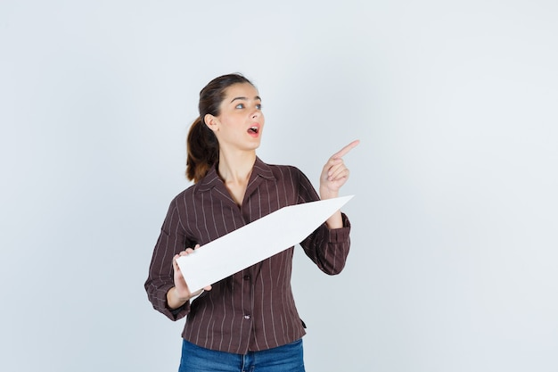Młoda dama w koszuli, dżinsy skierowane w górę, trzymając papierowy plakat i patrząc zdziwiony, widok z przodu.