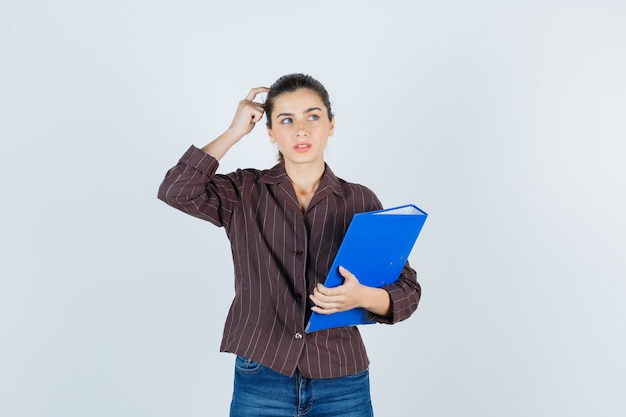 Młoda dama w koszuli, dżinsy trzymając folder, stojąc w pozie myślenia i patrząc rozsądnie, widok z przodu.