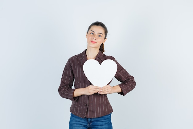 Młoda dama w koszuli, dżinsy trzymając papierowy plakat i wyglądający pięknie, widok z przodu.
