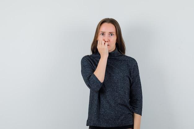 Młoda dama w koszuli gryzie paznokcie emocjonalnie i wygląda na zaniepokojoną