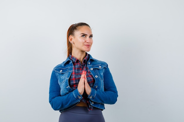 Młoda dama w koszuli, kurtce pokazującej gest namaste i patrząc z nadzieją, widok z przodu.