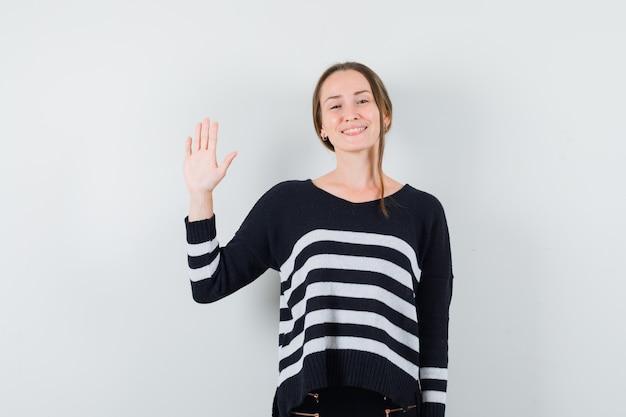 Młoda dama w koszuli na co dzień macha ręką na powitanie i patrzy wesoło