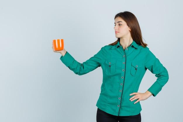 Młoda dama w koszuli pozowanie, trzymając pomarańczową filiżankę herbaty i patrząc pewnie, widok z przodu.
