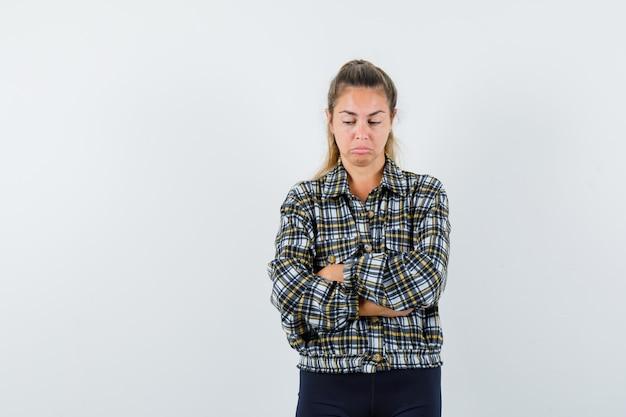 Młoda dama w koszuli, spodenkach stojących ze skrzyżowanymi rękami i wyglądających na obrażonych, widok z przodu.