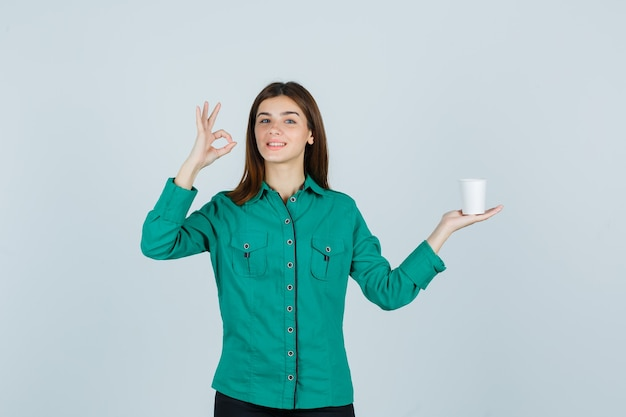 Młoda dama w koszuli trzyma plastikową filiżankę kawy, pokazując ok gest i patrząc wesoło, widok z przodu.