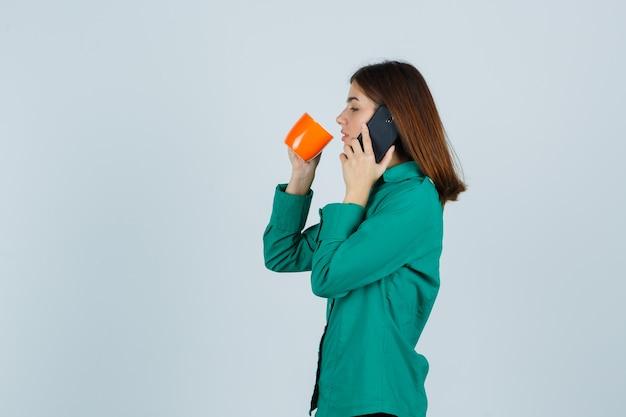 Młoda dama w koszuli trzyma pomarańczową filiżankę herbaty, rozmawia przez telefon komórkowy i wygląda pewnie, widok z przodu.