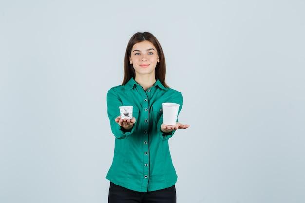 Młoda dama w koszuli, trzymając plastikowe filiżanki kawy i patrząc zadowolony, widok z przodu.