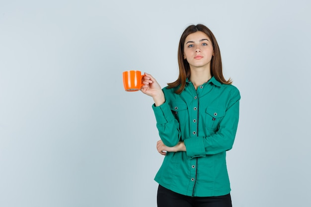 Młoda dama w koszuli, trzymając pomarańczową filiżankę herbaty i patrząc pewnie, z przodu.