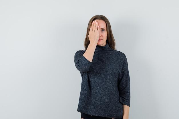 Młoda dama w koszuli, trzymając rękę na oku i patrząc zaciekawiony