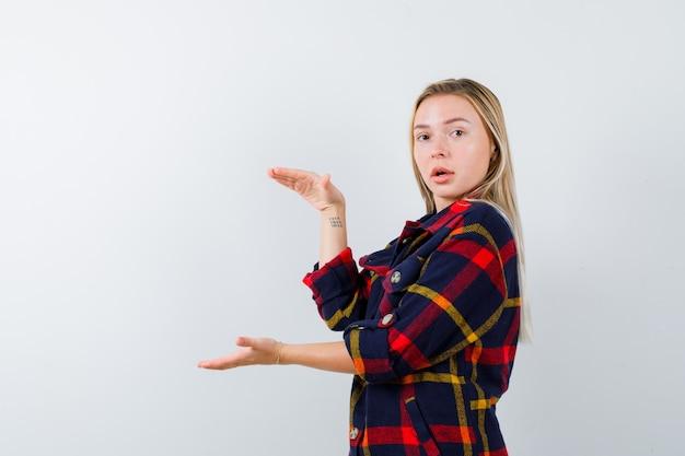 Młoda dama w koszuli w kratę, pokazująca znak rozmiaru i wyglądająca na zdziwioną, widok z przodu.