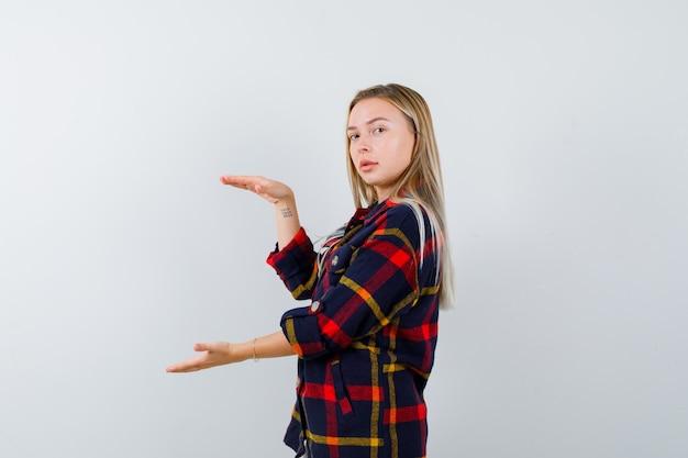 Młoda dama w koszuli w kratę pokazująca znak rozmiaru, patrząc przez ramię i wyglądająca na pewną siebie, widok z przodu.