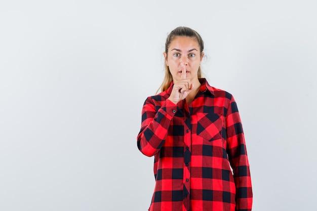 Młoda dama w koszuli w kratę pokazuje gest ciszy i patrzy uważnie