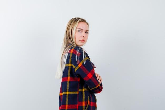 Młoda dama w koszuli w kratę, stojąca ze skrzyżowanymi rękami, patrząc przez ramię i pewna siebie, widok z przodu.