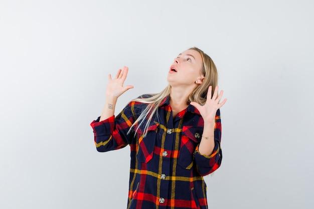 Młoda dama w koszuli w kratkę pokazująca dłonie w geście kapitulacji, patrząc w górę i patrząc zdziwiona, widok z przodu.