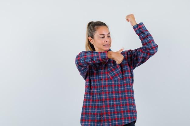 Młoda dama w koszuli w kratkę pokazuje mięśnie z kciukiem do góry i wygląda pewnie, widok z przodu.