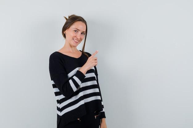Młoda dama w koszuli wskazująca na prawy górny róg i wyglądająca radośnie