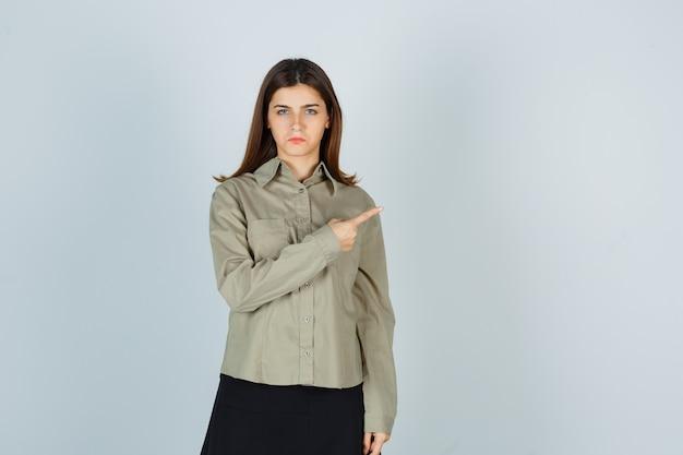 Młoda dama w koszuli, ze spódnicą skierowaną w prawy górny róg i wyglądająca na rozczarowaną