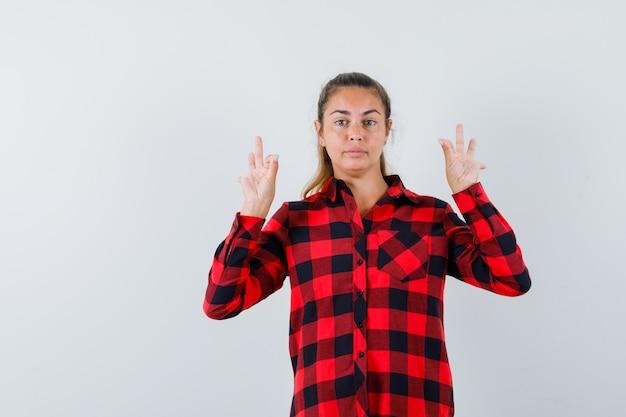 Młoda dama w kraciastej koszuli pokazuje gest medytacji i wygląda pewnie