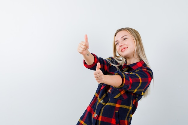 Młoda dama w kraciastej koszuli pokazuje kciuki do góry i wygląda na szczęśliwą, widok z przodu.