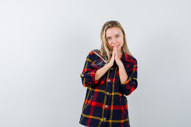 Młoda dama w kraciastej koszuli ściskająca dłonie do modlitwy i wyglądająca spokojnie, widok z przodu.