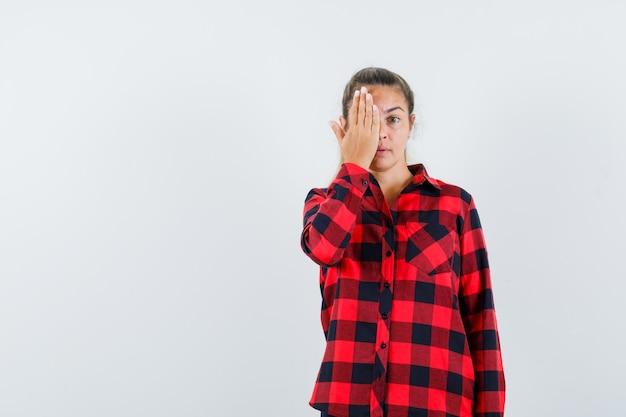 Młoda dama w kraciastej koszuli trzyma rękę na oku i wygląda pięknie