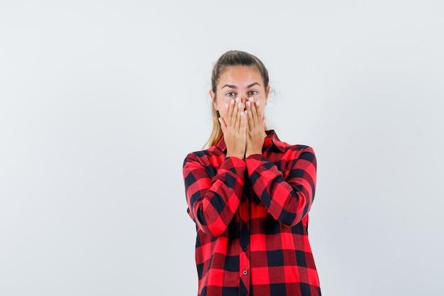Młoda dama w kraciastej koszuli, trzymając się za ręce na ustach i patrząc podekscytowany